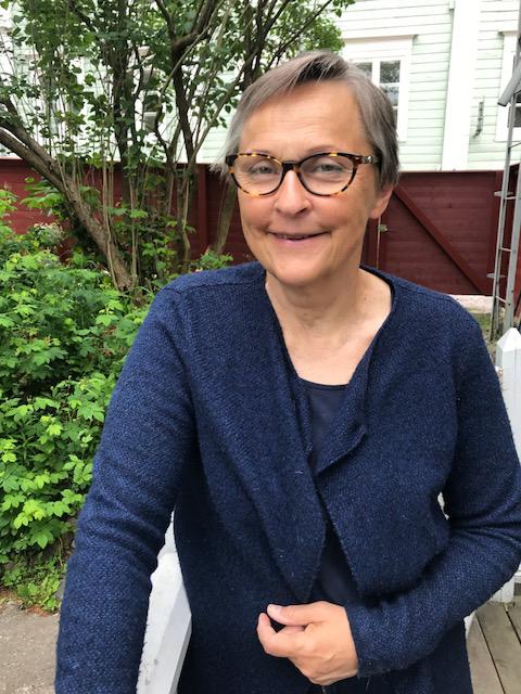 Taiteilija Liisa Malmio poseeraa terassilla kesäpäivänä Porvoon vanhassa kaupungissa.