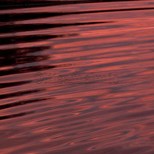 auringonlaskun punainen sävy heijastuu meren pintaan Korppoossa